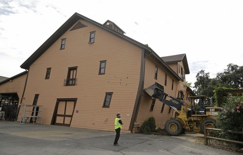Construction manager Joe Griego looks at the heavy equipment brought in to support the leaning earthquake damaged historic winery building at Trefethen Family Vineyards Friday, Aug. 29, 2014, in Napa, Calif. Harvest resumed at the winery on Friday in addition to the arrival of crews to shore up the historic building that dates from 1886. The 6.0-earthquake that damaged buildings and left scores of people injured in California's wine country was the largest temblor to hit the San Francisco Bay Area since the 6.9-magnitude Loma Prieta earthquake in 1989. (AP Photo/Eric Risberg)