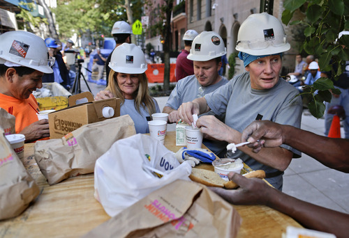 In this Aug. 14, 2014 photo, Anne White, right, and Felicia Zerilli, second from left, take a coffee break with co-workers on a construction site where they work, in New York. Zerilli, a shop steward, and White, a laborer, are two of 220 women in the 7,000 member Laborers Local 79 union. The latest federal data shows about 7.1 million Americans were employed in construction-related occupations last year and only 2.6 percent were women. (AP Photo/Julie Jacobson)