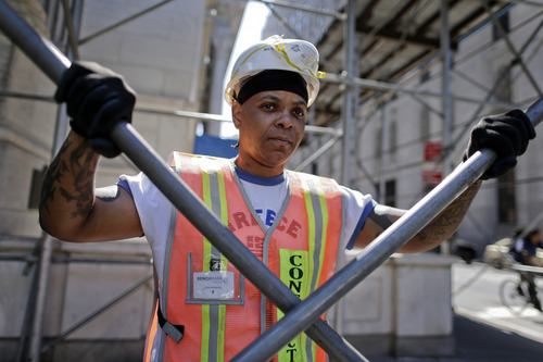 In this Aug. 14, 2014 photo, Sophia Johnson stands for a photo outside a construction site where she works as a shop steward, in New York. The latest federal data shows about 7.1 million Americans were employed in construction-related occupations in 2013, and only 2.6 percent were women. (AP Photo/Julie Jacobson)