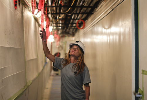 In this Aug. 14, 2014 photo, Felicia Zerilli gazes at a group of conduits while walking down a hallway at a construction site where she works as a shop steward, in New York. The latest federal data shows about 7.1 million Americans were employed in construction-related occupations last year and only 2.6 percent were women. (AP Photo/Julie Jacobson)