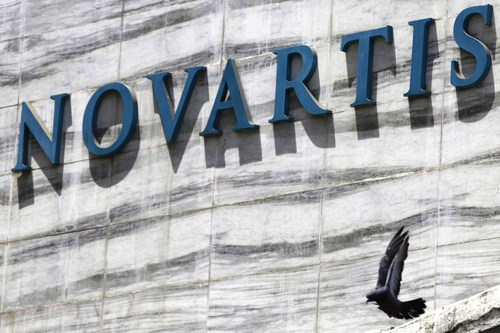 FILE - In this April 1, 2013 file photo, a dove flies near the logo of Novartis India Limited at their head office in Mumbai, India. A new study released Saturday, Aug. 30, 2014, shows an experimental Novartis drug, which does not have a name, lowered the chances of death or hospitalization by about 20 percent. (AP Photo/Rafiq Maqbool, File)