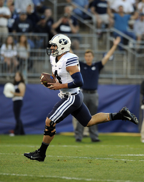 BYU quarterback Taysom Hill (4) runs for a touchdown during an NCAA college football game against Connecticut, Friday, Aug. 29, 2014. (AP Photo/Fred Beckham)
