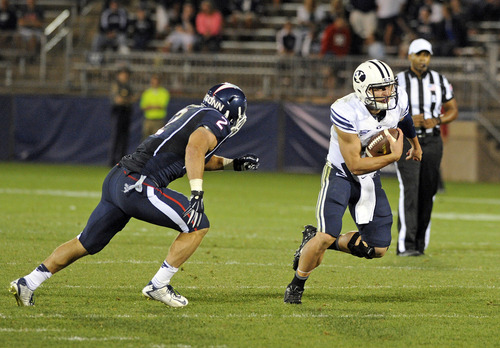 BYU quarterback Taysom Hill, front right, runs for a touchdown while pursued by Connecticut linebacker Graham Stewart (2) during the second half of BYU's 35-10 victory in an NCAA college football game in East Hartford, Conn., Friday, Aug. 29, 2014. (AP Photo/Fred Beckham)