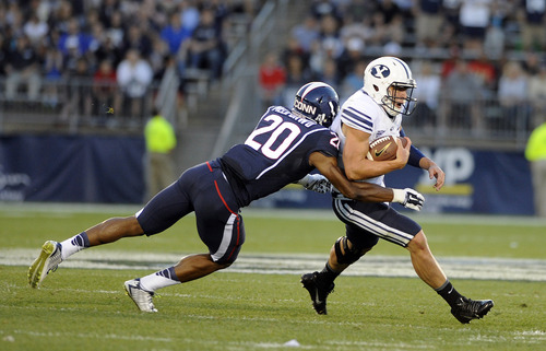 BYU quarterback Taysom Hill (4) runs for a first down while being pursued by Connecticut safety Obi Melifonwu (20) during the first half of an NCAA college football game in East Hartford, Conn., Friday, Aug. 29, 2014. (AP Photo/Fred Beckham)