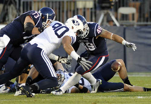 Connecticut tight end Sean McQuillan (49) and BYU tight end Matt Sumsion (80) fight for a loose ball after a Connecticut fumble during the first half of an NCAA college football game in East Hartford, Conn., Friday, Aug. 29, 2014. (AP Photo/Fred Beckham)
