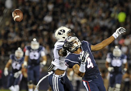 Connecticut wide receiver Deshon Foxx (4) is covered by BYU cornerback Michael Davis during the first half of an NCAA college football game in East Hartford, Conn., on Friday, Aug. 29, 2014. (AP Photo/Fred Beckham)