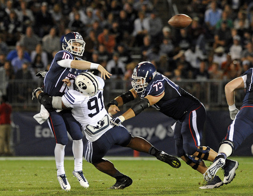 Connecticut quarterback Casey Cochran (12) is pressured by BYU defensive lineman Travis Tuiloma (91) during the first half of an NCAA college football game in East Hartford, Conn., on Friday, Aug. 29, 2014. (AP Photo/Fred Beckham)