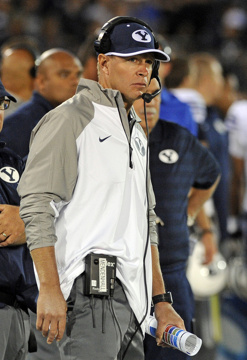 BYU head coach Bronco Mendenhall looks on during the first half of an NCAA college football game against Connecticut in East Hartford, Conn., Friday, Aug. 29, 2014. (AP Photo/Fred Beckham)