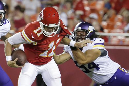 Minnesota Vikings defensive end Justin Trattou (94) sacks Kansas City Chiefs quarterback Alex Smith (11) during the second half of an NFL preseason football game in Kansas City, Mo., Saturday, Aug. 23, 2014. (AP Photo/Charlie Riedel)