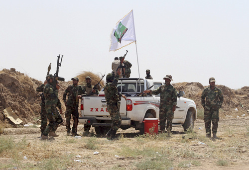 Iraqi security forces and Shiite militiamen chant anti-terrorism slogans after breaking the siege on 15,000 Shiite Turkmens stranded in the farming community town of Amirli, following U.S. airstrikes against Sunni Islamic State group positions, 105 miles (170 kilometers) north of Baghdad, Sunday, Aug. 31, 2014. The Islamic State extremist group has seized cities, towns and vast tracts of land in northeastern Syria and northern and western Iraq. It views Shiites as apostates and has carried out a number of massacres and beheadings — often posting grisly videos and photos of the atrocities online. (AP Photo)