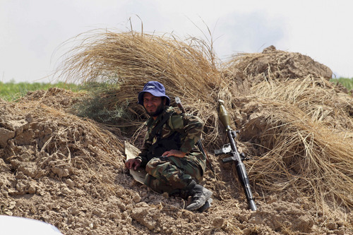 A Shiite militiaman takes a rest after Iraqi security forces and Shiite militiamen broke a six-week siege imposed by the Islamic State extremist group on the northern Shiite Turkmen town of Amirli, following U.S. airstrikes against the Sunni militants' positions, 105 miles (170 kilometers) north of Baghdad, Sunday, Aug. 31, 2014. The Islamic State extremist group has seized cities, towns and vast tracts of land in northeastern Syria and northern and western Iraq. It views Shiites as apostates and has carried out a number of massacres and beheadings — often posting grisly videos and photos of the atrocities online.  (AP Photo)