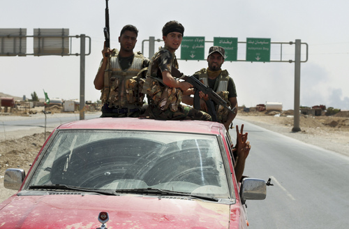 Shiite militiamen patrol in Amirli, Iraq, after breaking a siege by the Islamic State extremist group on the town, some 105 miles (170 kilometers) north of Baghdad, Sunday, Aug. 31, 2014. Iraqi security forces and Shiite militiamen on Sunday broke the six-week siege imposed by the Islamic State group on the northern Shiite Turkmen town of Amirli, following U.S. airstrikes against the Sunni militants' positions, officials said. (AP Photo)