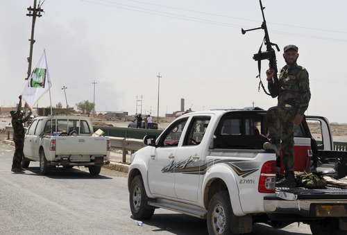 Shiite militiamen patrol in Amirli, 105 miles (170 kilometers) north of Baghdad, Iraq, Sunday, Aug. 31, 2014. Iraqi security forces and Shiite militiamen on Sunday broke a six-week siege imposed by the Islamic State extremist group on the northern Shiite Turkmen town of Amirli, following U.S. airstrikes against the Sunni militants' positions, officials said. (AP Photo)