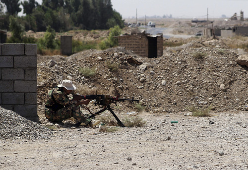 A Shiite militiaman takes his combat position in Amirli, 105 miles (170 kilometers) north of Baghdad, Iraq, Sunday, Aug. 31, 2014. Iraqi security forces and Shiite militiamen on Sunday broke a six-week siege imposed by the Islamic State extremist group on the northern Shiite Turkmen town of Amirli, following U.S. airstrikes against the Sunni militants' positions, officials said. (AP Photo)