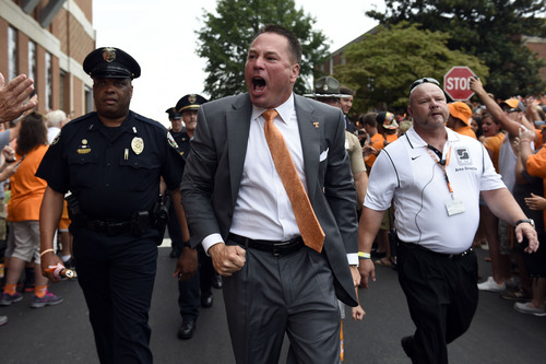 Tennessee head coach Butch Jones, center, yells to fans during the Vol Walk before an NCAA college football game against Utah State, Sunday, Aug. 31, 2014, in Knoxville, Tenn. (AP Photo/The Knoxville News Sentinel, Saul Young)