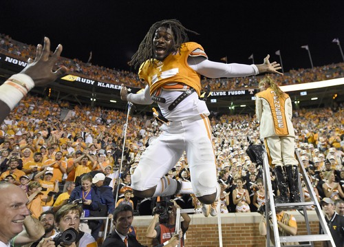 Tennessee linebacker A.J. Johnson (45) leaps off a stepladder in celebration after Tennessee beat Utah State 38-7 at Neyland Stadium, Sunday, Aug. 31, 2014 in Knoxville, Tenn.  (AP Photo/Knoxville News Sentinel, Adam Lau)