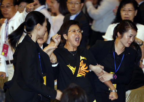 "Pro-democracy lawmaker Helena Wong Pik-wan, center, is taken away by security guards after a protest against Li Fei, deputy secretary general of the National People's Congress' Standing Committee, during a briefing session in Hong Kong Monday, Sept. 1, 2014. China's legislature on Sunday ruled out allowing open nominations in the inaugural election for Hong Kong's leader, saying they would create a ""chaotic society."" Democracy activists in the Asian financial hub responded by saying that a long-threatened mass occupation of the heart of the city ""will definitely happen."" (AP Photo/Kin Cheung)"