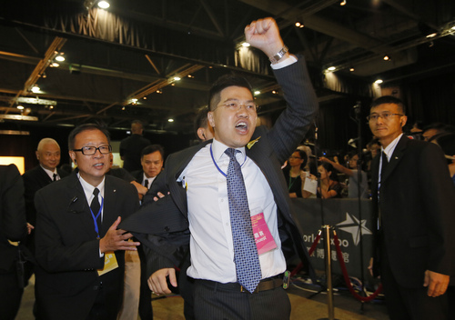 "Pro-democracy lawmaker Gary Fan Kwok-wai, center, is taken away by security guards after a protest against Li Fei, deputy secretary general of the National People's Congress Standing Committee, in Hong Kong Monday, Sept. 1, 2014. China's legislature on Sunday ruled out allowing open nominations in the inaugural election for Hong Kong's leader, saying they would create a ""chaotic society."" Democracy activists in the Asian financial hub responded by saying that a long-threatened mass occupation of the heart of the city ""will definitely happen."" (AP Photo/Vincent Yu)"
