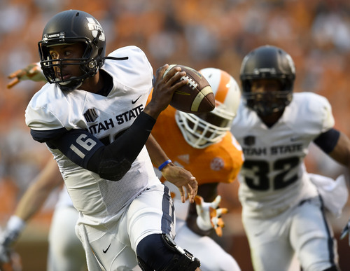 Utah State quarterback Chuckie Keeton (16) tries to get away from a Tennessee defender during their NCAA college football game at Neyland Stadium, Sunday, Aug. 31, 2014 in Knoxville, Tenn.  (AP Photo/Knoxville News Sentinel, Amy Smotherman Burgess)