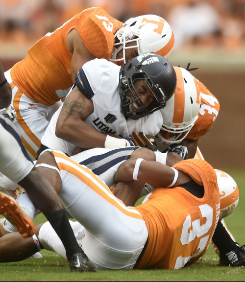 Utah State wide receiver Brandon Swindall (11) is tackled by Tennessee defensive back Devaun Swafford (13), linebacker Jalen Reeves-Maybin (34), and, defensive back Brian Randolph (37) during their NCAA college football game against Utah State at Neyland Stadium, Sunday, Aug. 31, 2014 in Knoxville, Tenn.  (AP Photo/Knoxville News Sentinel, Saul Young)