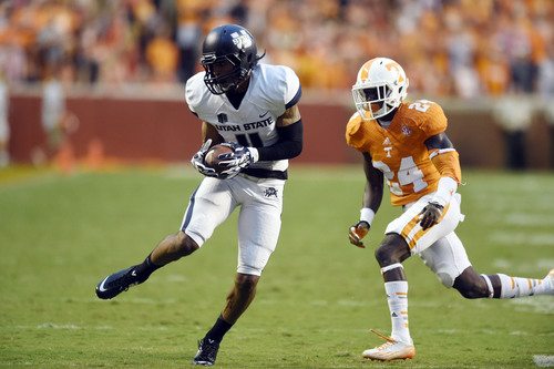 Utah State wide receiver Brandon Swindall (11) makes a reception just as he is about to be tackle by Tennessee defensive back Michael Williams (24) during the first quarter of the game against Utah State at Neyland Stadium, Sunday, Aug. 31, 2014 in Knoxville, Tenn.    (SAUL YOUNG/NEWS SENTINEL)