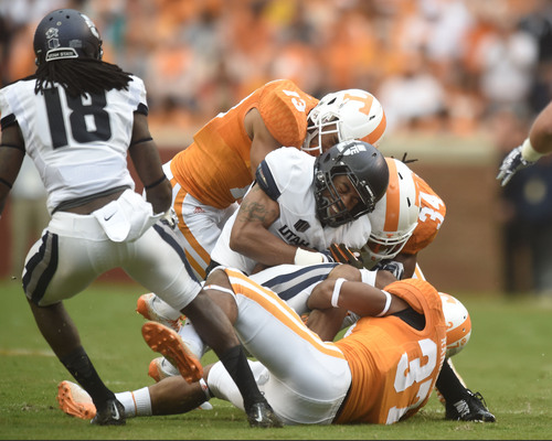 Utah State wide receiver Brandon Swindall (11) is tackled by, from left, Tennessee defensive back Devaun Swafford (13), linebacker Jalen Reeves-Maybin (34), and, defensive back Brian Randolph (37) during the first quarter of the game against Utah State at Neyland Stadium, Sunday, Aug. 31, 2014 in Knoxville, Tenn.    (SAUL YOUNG/NEWS SENTINEL)