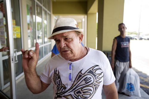 """In this Thursday, Aug. 28, 2014 photo, Pedro Rosa, of Havana, discusses a new trade policy, as he stands outside a Miami discount clothing store. Rosa planned to return to Cuba before new Cuban rules go into effect sharply limiting the amount of goods people can bring in on flights from abroad, an attempt to shut down the """"mule"""" business that's feeding tons of new private enterprise in Cuba.  (AP Photo/J Pat Carter)"""