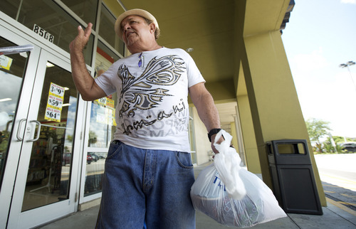 In this Thursday, Aug. 28, 2014 photo, Pedro Rosa, of Havana, discusses a new trade policy, as he stands outside a Miami discount clothing store. Rosa planned to return to Cuba before new Cuban rules go into effect sharply limiting the amount of goods people can bring in on flights from abroad, an attempt to shut down the 'mule' business that's feeding tons of new private enterprise in Cuba.  (AP Photo/J Pat Carter)