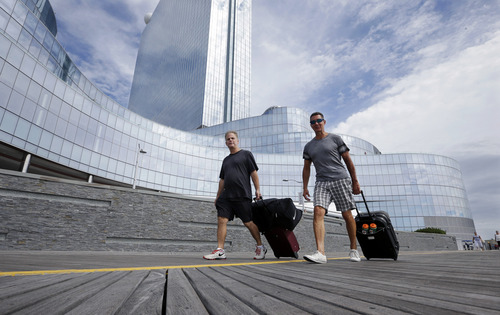 Randy Chapman, left, of California, and John Krisel, of New York, walk on The Boardwalk after they checked out of the closing Revel Casino Hotel Monday, Sept. 1, 2014, in Atlantic City, N.J. The most spectacular and costly failure in Atlantic City's 36-year history of casino gambling began to play out Monday when the $2.4 billion Revel Casino Hotel emptied its hotel. Its casino will close early Tuesday morning. Revel is shutting down a little over two years after opening with high hopes of revitalizing Atlantic City's struggling gambling market. (AP Photo/Mel Evans)