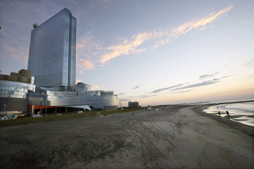 People walk on the beach near The Boardwalk entrance to the Revel Hotel Casino early Tuesday, Sept. 2, 2014, in Atlantic City, N.J. The casino section of the Revel closed at 6:30 a.m. Tuesday. Revel is shutting down a little over two years after opening with high hopes of revitalizing Atlantic City's struggling gambling market. (AP Photo/Mel Evans)
