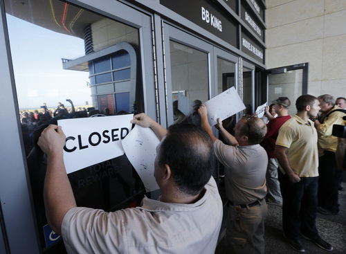 Workers put closed signs on the entrance of the Showboat Casino Hotel Sunday, Aug. 31, 2014, in Atlantic City, N.J. The show is ending for the Showboat Casino Hotel in Atlantic City. The Mardi Gras-themed casino is shutting down at 4 p.m. Sunday after 27 years on the Boardwalk. Owner Caesars Entertainment is closing the still-profitable Showboat to reduce the number of casinos in Atlantic City, which has been struggling with plunging revenue and increased competition. (AP Photo/Mel Evans)