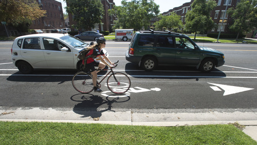 Steve Griffin     The Salt Lake Tribune   A cyclist travels in the bike lane between the curb and parked cars on 300 South near 300 east in Salt Lake City, Friday, August 29, 2014.  Protected bike lanes from 600 East to 300 West will require the loss of about one-third of curbside parking because angle parking will change to parallel parking to make room for the bike lanes.
