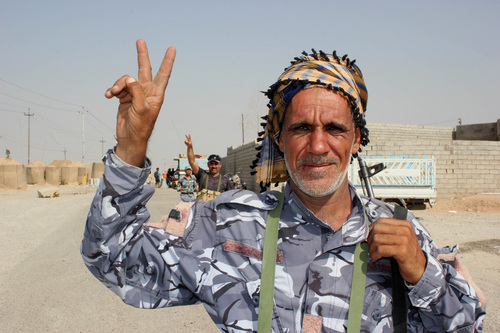 In this Monday, Sept. 1, 2014 photo, Shiite militiamen flash victory signs during an operation outside Amirli, some 105 miles (170 kilometers) north of Baghdad, Iraq. Aid began flowing into the small northern Shiite town in Iraq on Monday, a day after security forces backed by Iran-allied Shiite militias and U.S. airstrikes broke a two-month siege by insurgents in a rare victory by government forces. (AP Photo)
