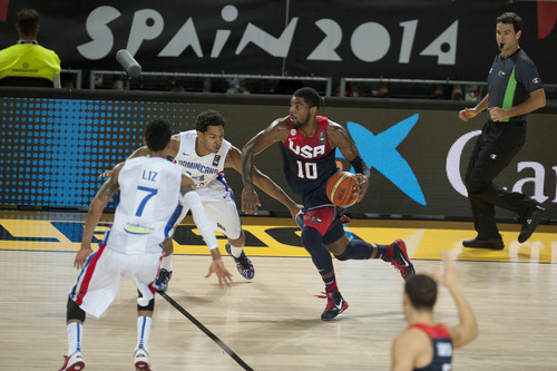 United States's Kyrie Irving, center right, controls the ball in front Dominican Republic's Ronald Ramon during the Group C Basketball World Cup match, in Bilbao northern Spain, Wednesday, Sept. 3, 2014. The 2014 Basketball World Cup competition take place in various cities in Spain from Aug. 30 to Sept. 14. (AP Photo/Alvaro Barrientos)