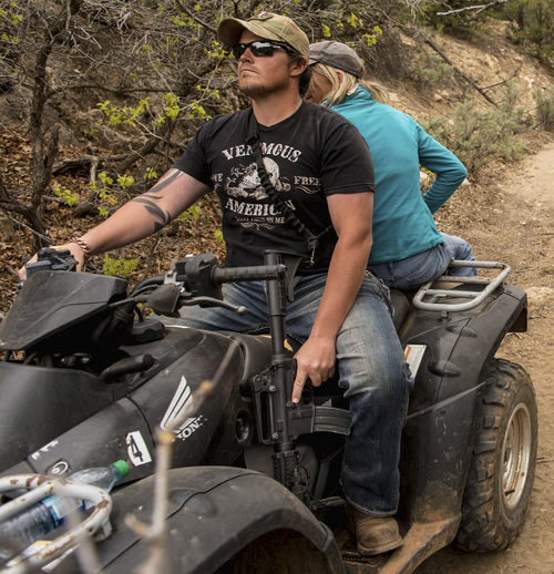 Trent Nelson  |  The Salt Lake Tribune A rider holds his finger off the trigger of his assault rifle as motorized vehicles make their way through Recapture Canyon, which has been closed to motorized use since 2007, after a call to action by San Juan County Commissioner Phil Lyman. Saturday May 10, 2014 north of Blanding.