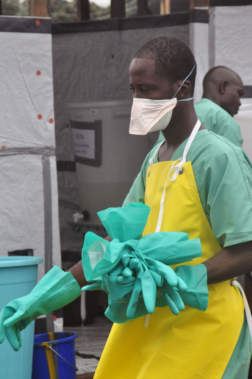 FILE - This Aug. 18, 2014 file photo shows a health worker carrying gloves at an Ebola treatment center in the city of Monrovia, Liberia. President Barack Obama urged West Africans on Tuesday to wear gloves and masks when caring for Ebola patients or burying anyone who died of the disease. He also discouraged the traditional burial practice of directly touching the body of someone who died of Ebola, which is one way the disease has been spreading in the region. (AP Photo/Abbas Dulleh, File)