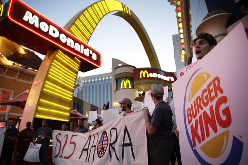 Protestors, including Kris Varrette, right, chant for increased wages and union rights at fast food restaurants Thursday, Sept. 4, 2014, in Las Vegas. Police detained several protesters in cities nationwide Thursday as they blocked traffic in the latest attempt to escalate their efforts to get McDonald's, Burger King and other fast-food companies to pay their employees at least $15 an hour. (AP Photo/John Locher)