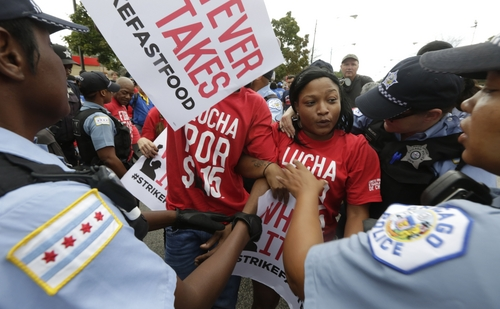 Chicago police remove protesters from the middle of 87th street between a McDonald's and a Burger King on Chicago's south side as labor organizers escalate their campaign to unionize the industry's workers, Thursday, Sept. 4, 2014. Police detained several protesters in cities nationwide Thursday as they blocked traffic in the latest attempt to escalate their efforts to get McDonald's, Burger King and other fast-food companies to pay their employees at least $15 an hour. (AP Photo/M. Spencer Green)