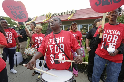 Carmalita Johnson drums as protesters participate in a rally outside a McDonald's on Chicago's south side as labor organizers escalate their campaign to unionize the industry's workers Thursday, Sept. 4, 2014. Hundreds of workers from McDonald's, Taco Bell, Wendy's and other fast-food chains are expected to walk off their jobs Thursday, according to labor organizers of the latest national protest to push the companies to pay their employees at least $15 an hour.  (AP Photo/M. Spencer Green)