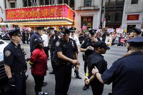Police officers arrest two protesters in front of a McDonald's restaurant on 42nd Street in New York's Times Square as police officers move in to begin making arrests, Thursday, Sept. 4, 2014. The protesters are seeking to get pay increases to $15 per hour. Thursday's demonstration is part of a day of planned protests in 150 cities across the country by workers from fast-food chains. (AP Photo/Mark Lennihan)