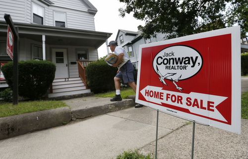 In this July 10, 2014 photo, a mailman delivers mail to a house for sale in Quincy, Mass. Freddie Mac reports on average U.S. mortgage rates for this week on Thursday, Sept. 4, 2014 (AP Photo/Michael Dwyer)
