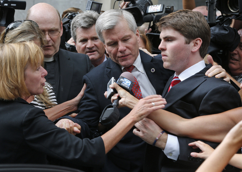 Former Virginia Gov. Bob McDonnell, center, is mobbed by media as he gets into a car with his son, Bobby, right, after he and his wife, former first lady Maureen McDonnell, were convicted on multiple counts of corruption at Federal Court in Richmond, Va., Thursday, Sept. 4, 2014. A federal jury in Richmond convicted Bob McDonnell of 11 of the 13 counts he faced; Maureen McDonnell was convicted of nine of the 13 counts she had faced. Sentencing was scheduled for Jan. 6.  (AP Photo/Steve Helber)