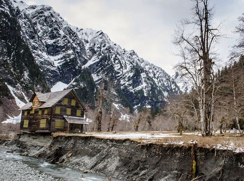 FILE - This April, 2014 file photo provided by the Olympic National Park service shows the Enchanted Valley Chalet, a log cabin on the eroding bank of the Quinault River in Olympic National Park in Washington. Park officials say a house mover is using equipment and possibly animals to pull the historic lodge away from the eroding edge of the river in the remote wilderness area. Good weather, Thursday, Sept. 4, 2014, should allow a helicopter to bring in any equipment that couldn't be carried by mules and horses. The animals might be used to drag the building 50 to 100 feet along steel beams. (AP Photo/Olympic National Park Service, File)