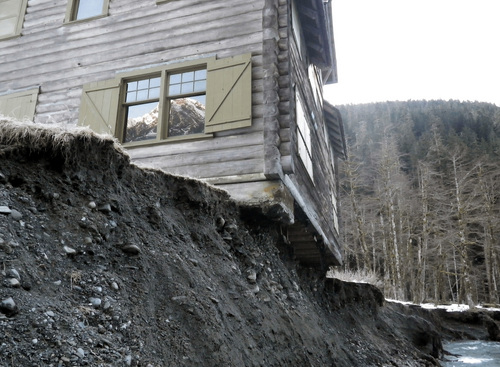 FILE - This March 12, 2014 file photo provided by Olympic National Park shows the Enchanted Valley Chalet, a log cabin on the eroding bank of the Quinault River in Olympic National Park in Washington. Park officials say a house mover is using equipment and possibly animals to pull the historic lodge away from the eroding edge of the river in the remote wilderness area. Good weather Thursday, Sept. 4, 2014, should allow a helicopter to bring in any equipment that couldn't be carried by mules and horses. The animals might be used to drag the building 50 to 100 feet along steel beams. (AP Photo/Olympic National Park Service, File)