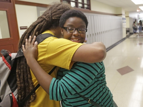 "In This Aug. 29, 2014, photo Erin Nwachukwu, right, hugs her friend Yosef Smith during orientation day at Lindblom Math and Science Academy in Chicago. A new study has found that, while Americans are mistrustful of each other and institutions -- from government to corporations and the media -- young people are among the least likely age group to have confidence in those institutions, especially since the terror attacks of Sept. 11, 2001. Nwachukwu, 16, says it's been difficult for her generation to keep the faith through multiple political scandals, a recession and various shootings — including the recent shooting of a young man in Ferguson, Missouri. ""We need more people who are setting a good example,"" Nwachukwu says. (AP Photo/M. Spencer Green)"