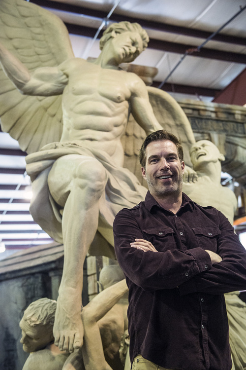 Chris Detrick  |  The Salt Lake Tribune CEO, Founder and Director Ken Bretschneider poses for a portrait with a sculpture of Michael Defeating the Devil that will be used in Evermore Adventure Park at their warehouse in Lindon on Wednesday Aug. 27, 2014.