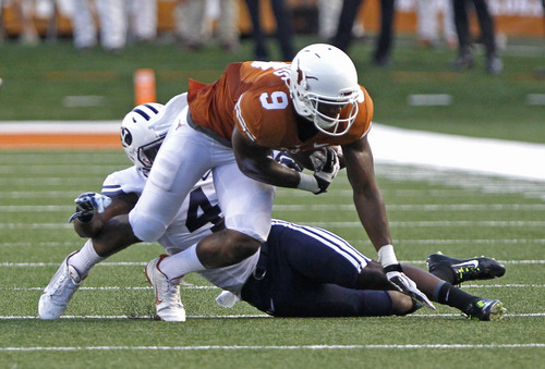 Texas receiver John Harris (9) fumbles the ball while being tackled by BYU's Robertson Daniel (4) during the second quarter of an NCAA college football game in Austin, Texas, Saturday,  Sept. 6, 2014.  (AP Photo/Michael Thomas)