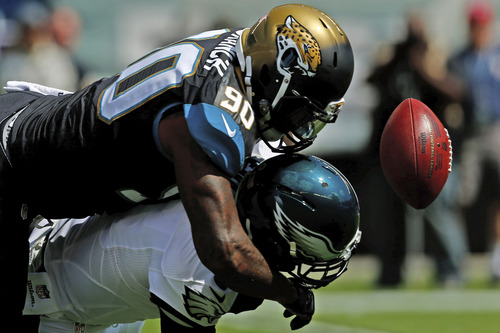 Philadelphia Eagles' Nick Foles, bottom, fumbles the football after a hit from Jacksonville Jaguars' Andre Branch during the first half of an NFL football game, Sunday, Sept. 7, 2014, in Philadelphia. (AP Photo/Michael Perez)