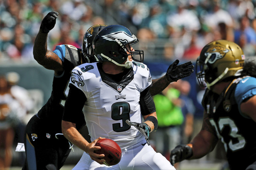 Philadelphia Eagles' Nick Foles, center, is pressured by Jacksonville Jaguars' Andre Branch, left, and Ziggy Hood during the first half of an NFL football game, Sunday, Sept. 7, 2014, in Philadelphia. (AP Photo/Michael Perez)