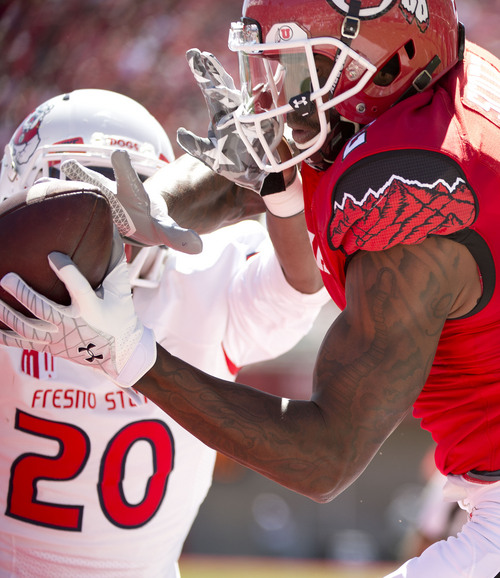 Jeremy Harmon  |  The Salt Lake Tribune  Utah's Kenneth Scott (2) catches the ball for a touchdown under pressure from Fresno State's Malcolm Washington (20) as the Utes host the Bulldogs at Rice-Eccles Stadium on Saturday, Sept. 6, 2014.
